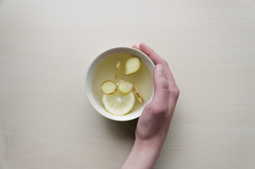 person holding a cup of lemon ginger tea during intermittent fasting