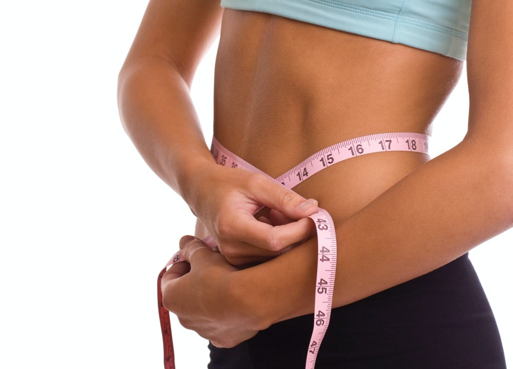 active woman measuring waist and reduced belly fat