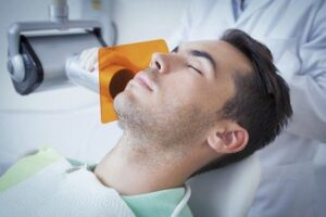 Man sleeping during xrays, using sedation therapy to relieve anxiety