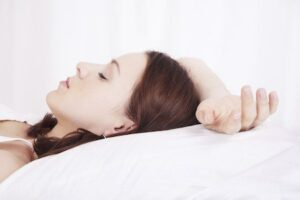 Young woman soundly sleeping after sleep dentistry treatment