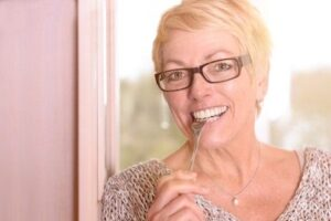 woman smiles with perfect looking teeth thanks to dentures