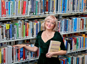 Library Director Kristine Kreidler, woman with pale blonde pink hair and wearing green dress in front of books. Woman is smiling and has her head cocked to towards the camera.