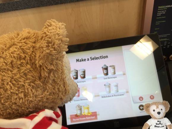 Duffy the Disney Bear orders his smoothie from a computer touch screen