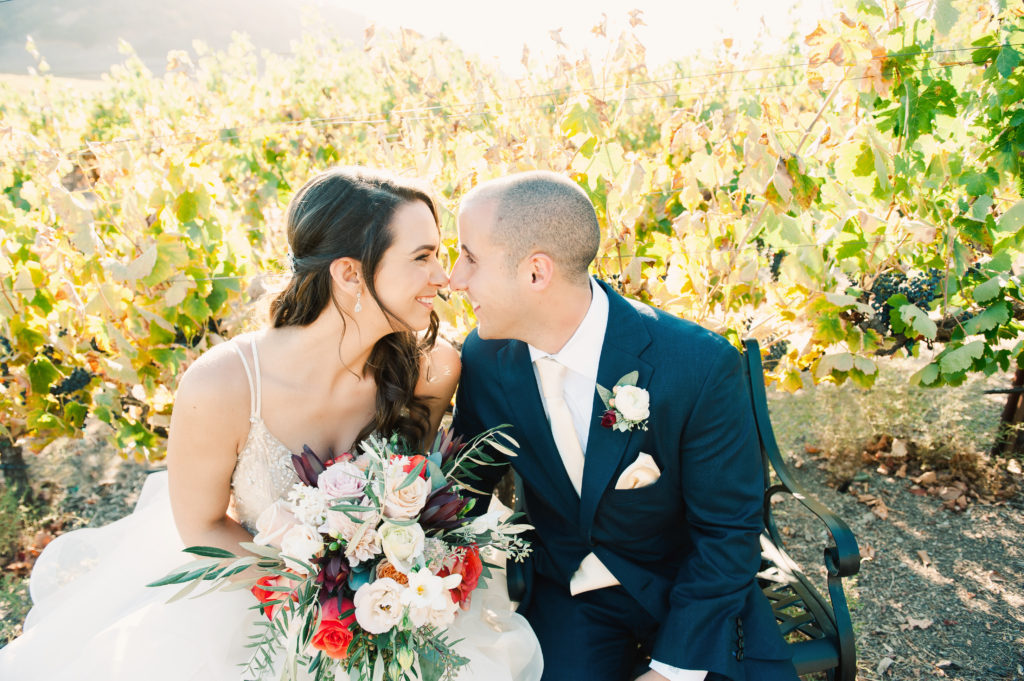 Bride and groom sitting in vineyards