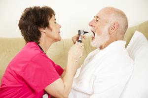 Home Nurse Examines Throat