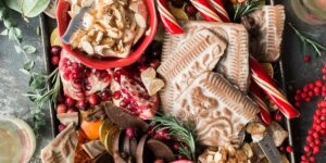 Against a grey background, a beautifully decorated tray of holiday goodies has candies, cookies, chocolates, and fruits on display.