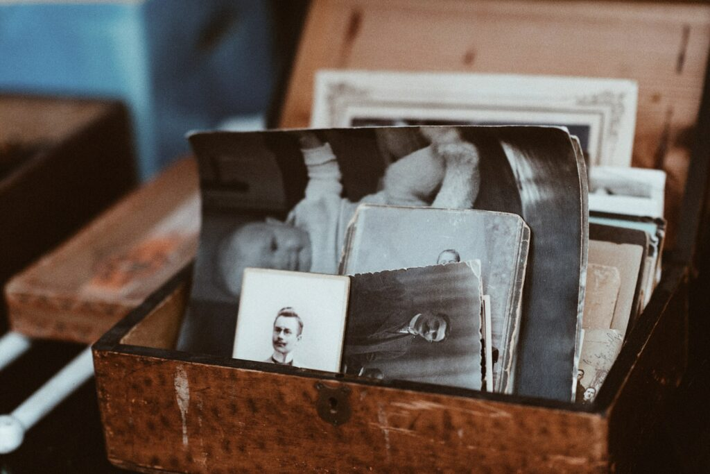 An old wooden box is open, showing stacks of old black and white photos inside.