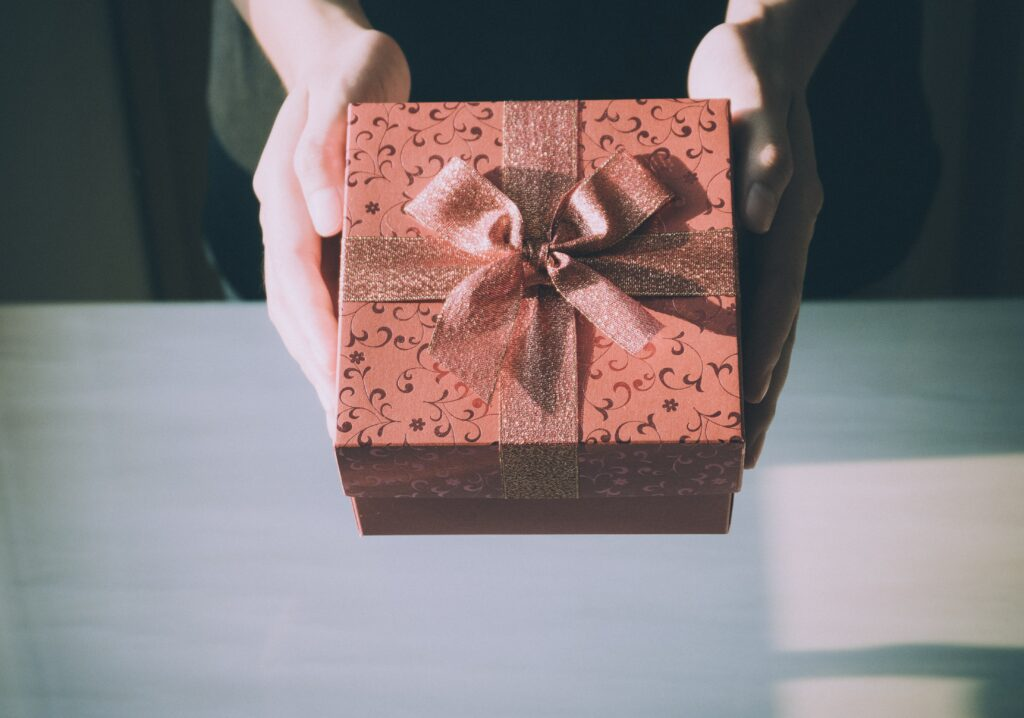 Two hands hold a pink or soft red gift box against a table background. The box is prettily decorated with metallic scroll patterns on the box itself as well as a shimmery ribbon tied around it.