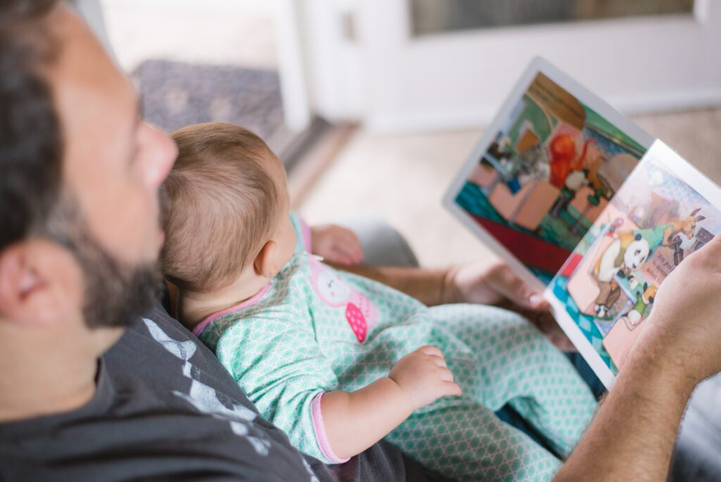 A father is reading a book to his baby/toddler