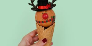 a hand is holding an ice cream cone with a round reindeer ornament sitting on it against a mint colored background