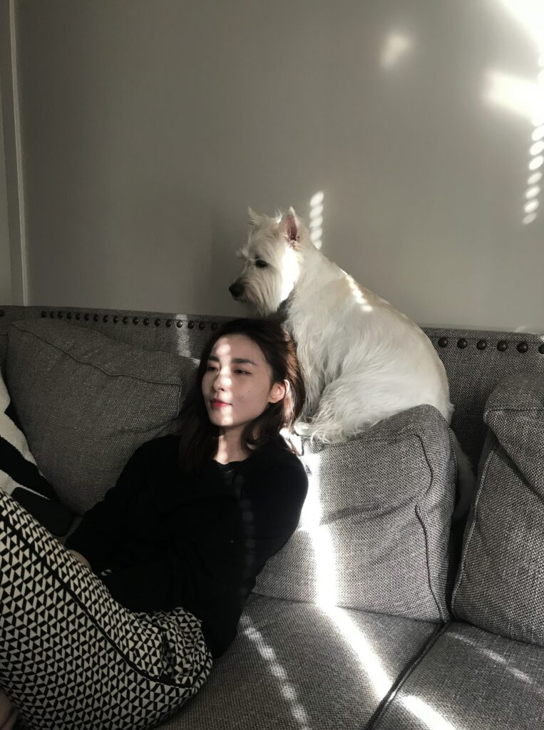 A woman is sitting on a couch watching a movie. Her dog is perched up on the back of the couch, half on her shoulder.