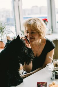 Woman Holding Treat for her black scottish terrier
