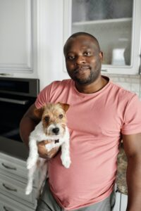 A man is holding a terrier puppy in his kitchen at home