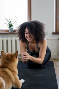 A smiling and laughing woman in workout gear is leaning forward, playing with her dog.