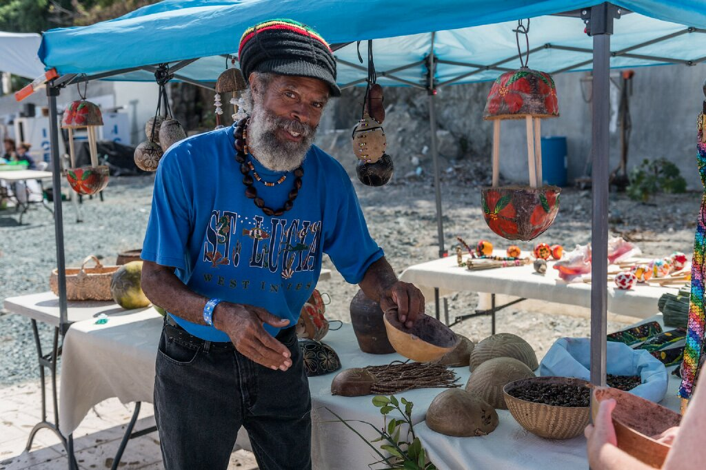 An old man offering wooden items