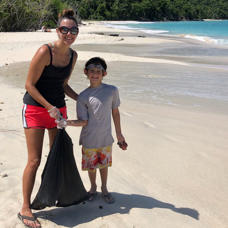 A woman with a boy holding a garbage bag