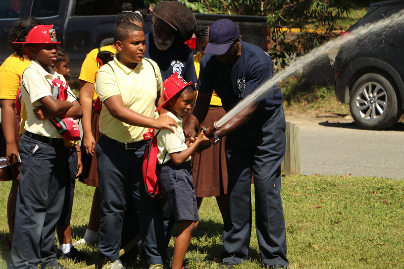 A child learning how to use a hose