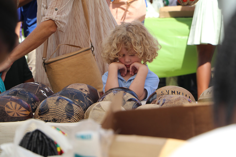 A child looking at wooden artifacts