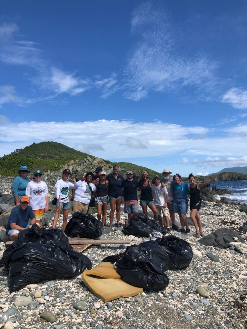 A group of visitors doing a beach cleanup