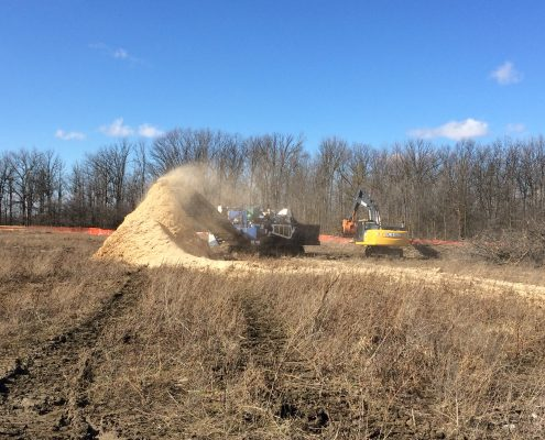 Excavator producing woodchips on site.