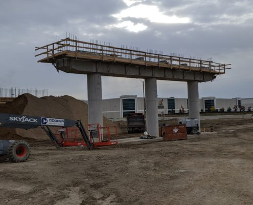 Photo showing the construction of piers that will support the future alignment of Zenway Boulevard