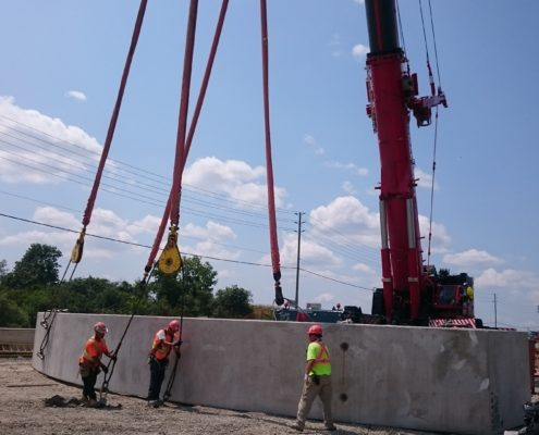 Workers prepare section of arch culvert for lifting.