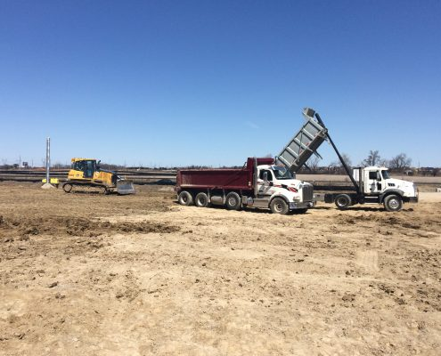 trucks moving earth during early works