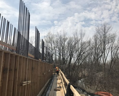 Bridge construction with worker at Rainbow Creek for bridge construction