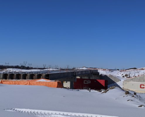 Photo showing construction in progress at the Highway 427 bridge over McGillivray Road and the CP Rail tracks