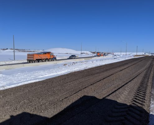 Photo of traffic driving on the new alignment of Major Mackenzie Drive near the Highway 427 interchange. The old alignment is visible in the foreground.
