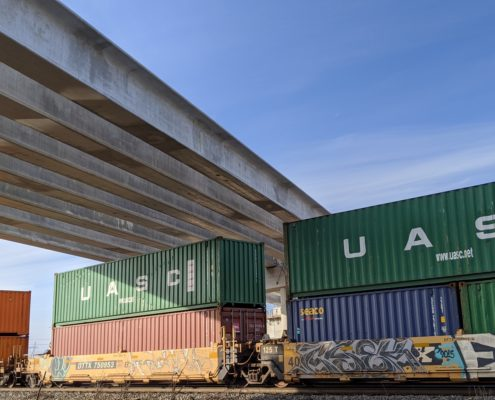 Photo of a freight train passing under the Highway 427 bridge over the CP Rail tracks