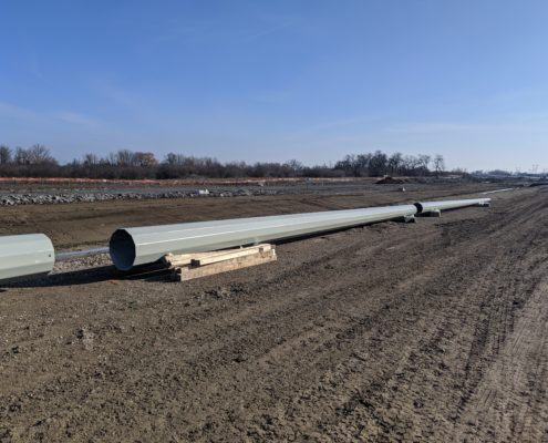 Photo of high mast light fixture poles stored near West Robinson Creek