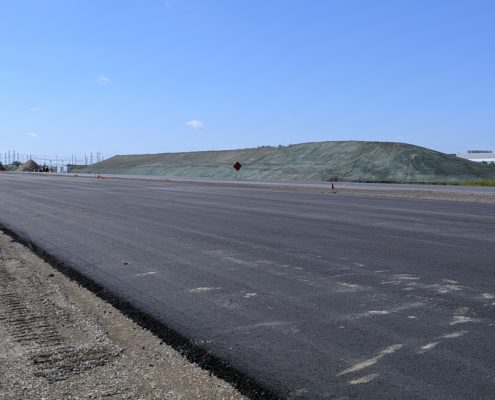 Paved roadway and seeded soil north of Zenway Boulevard