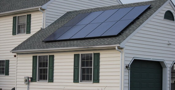 Dark solar panels on composite shingle roof without wiring conduits
