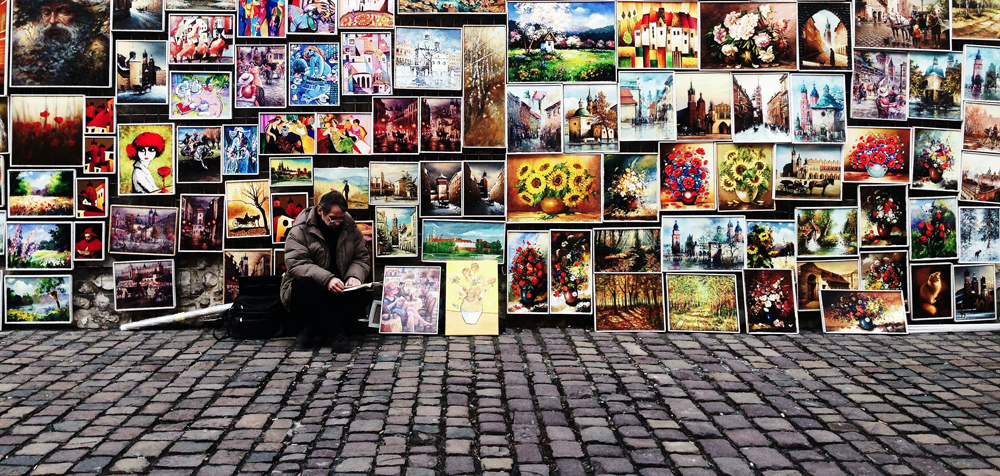 artist sitting on the street with paintings behind