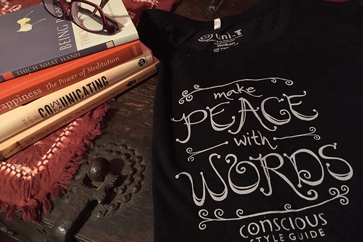 """Meditation books, glasses, and a T-shirt with a """"Make Peace With Words"""" hand-lettered design on a wooden trunk."""