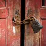 Closeup of rusty lock and chain on old double doors.