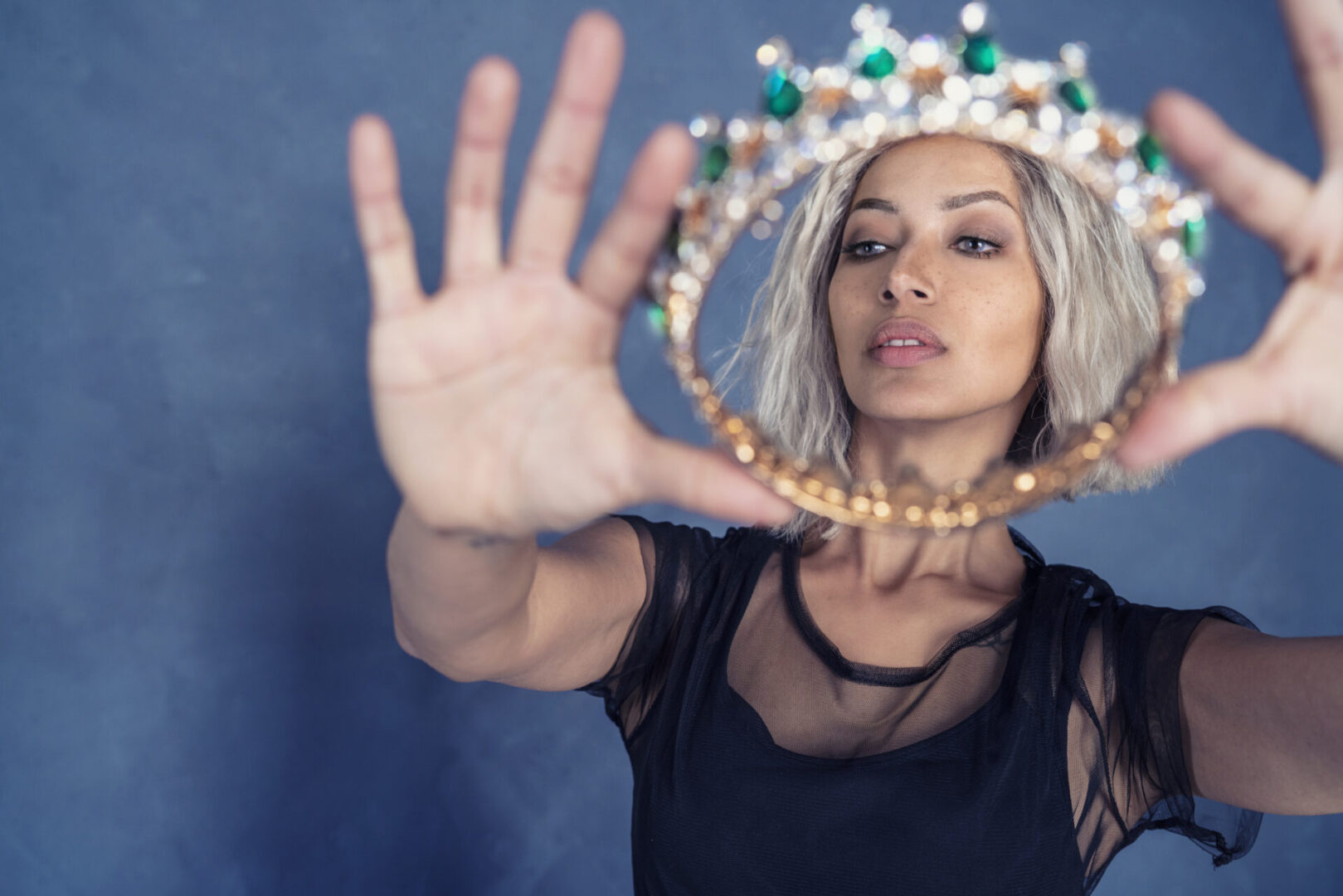 Fashion attractive blond woman holding crown as a queen of the night white trendy hair