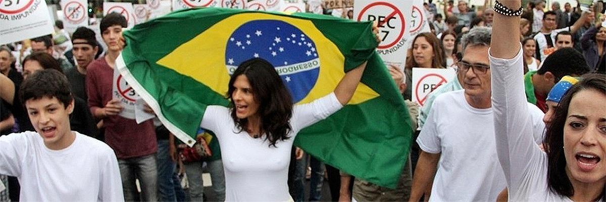 Jovem com bandeira do Brasil durante manifestação
