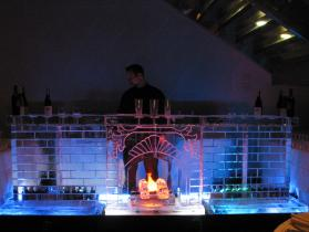 12 ft fireplace ice bar with theatrical flickering flame lighting in back of ice logs.
