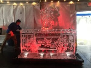 Merry Christmas Bar with drink luge on bar top. Bar has candy canes and holly frozen into bases