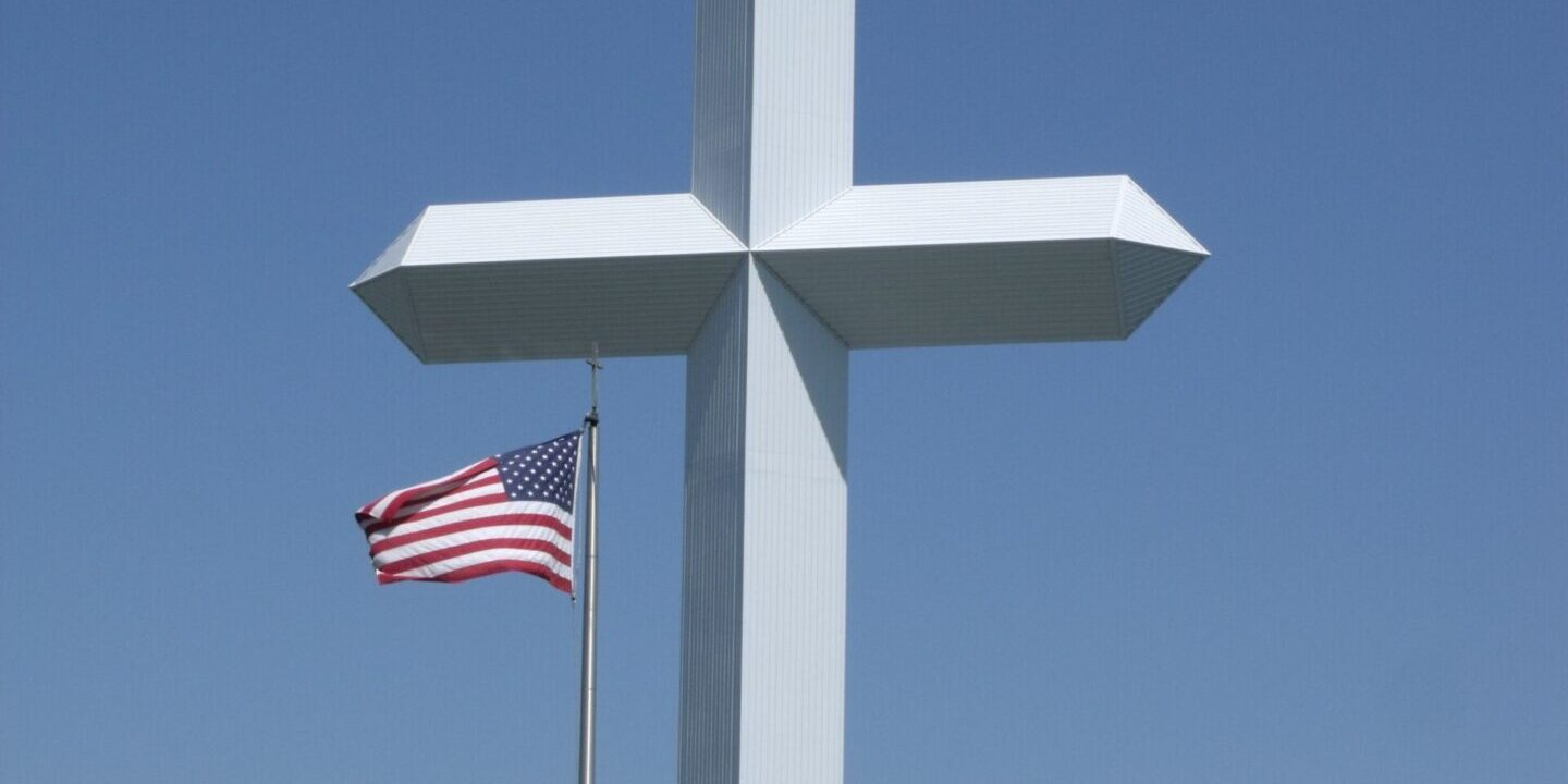 5887009 - large cross with us flag underneath and blue sky background