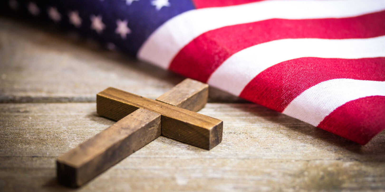 A holy wooden Christian cross laying on a wood background with an American flag.