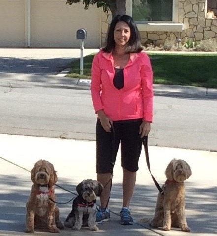 A woman standing with three small dogs.