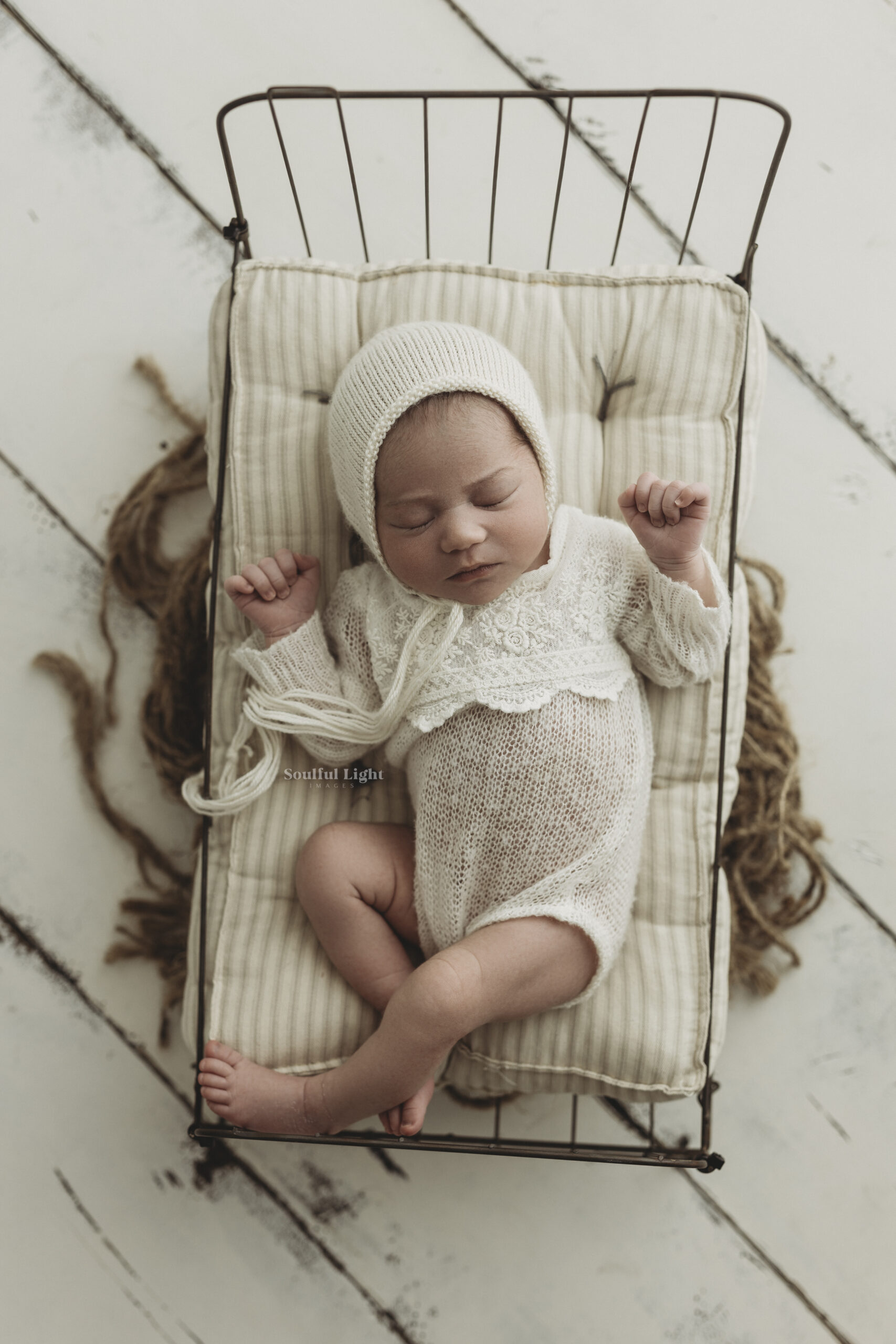 newborn baby girl with bonnet on bed prop