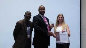 Kory May being presented Third Place by District Historian Reginald Williams and Division B Director Theresa Mickelson for the Humorous Speech Contest.