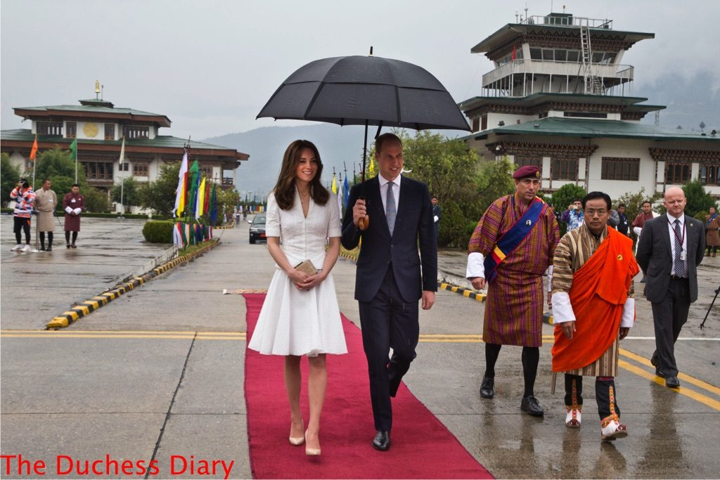 prince william holds umbrella kate middleton alexander mcqueen outfit leave Bhutan