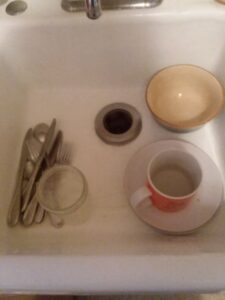 A sink with lots of empty space, a mug of silverware, one bowl, two plates, one glass jar and a cup.