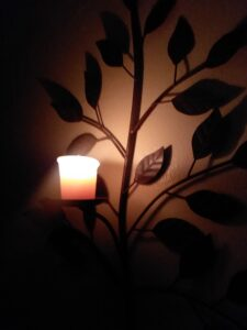 A small candle burns on a metal candle holder on a wall. The candleholder is shaped like a branch with leaves.