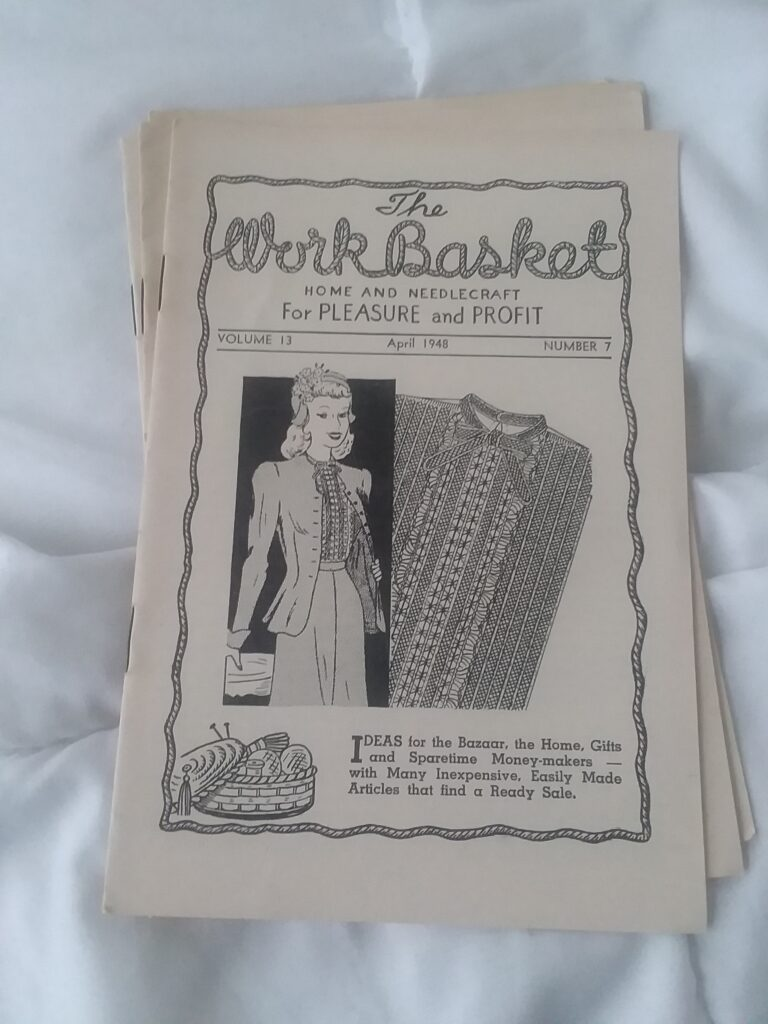 The Workbasket, a small magazine, printed on newsprint. Features a woman and a knitting project on the cover, a line drawing.
